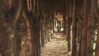 little girl run through the tunnel of trees. the child in the mysterious and magical forest. slow motion