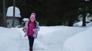 little girl running in the winter woods and smiling. Slow Motion