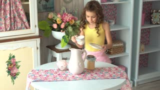 little girl sets the table. Small hostess is waiting for guests