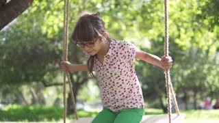 little girl swinging on a swing in summer Park. swing on ropes attached to the tree. a happy carefree childhood. slow motion