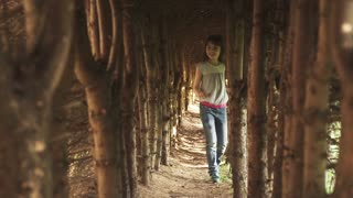 little girl walks through the tunnel of trees. the child in the mysterious and magical forest. slow motion