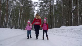 little girls are walking through the woods with my mother and holding hands.