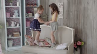 little girls girlfriends jumping on the couch and play. girl falls out of bed. slow motion