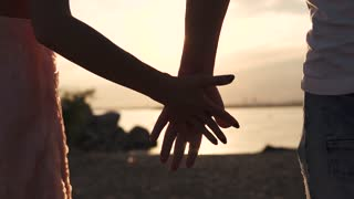 Male and female hand close-up against the setting sun. Gentle touch of two lovers. Love, romance, friendship
