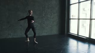male ballet dancer dancing against a dark background in the studio. slow motion