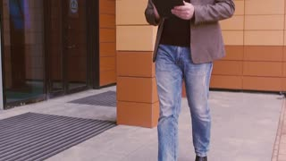 Modern businessman walking near business center and working on tablet computer. Man looks at a smart watch. Man in a jacket and glasses on the background of a modern business building.