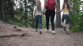 Mom with little daughters travel. Family of tourists on a walk in the forest