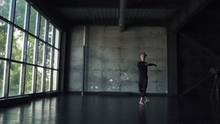 oung male ballet dancer dancing classical ballet in studio on a dark background. slow motion