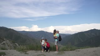 parents and their children travel to the mountains. father and mother holding hands on the young daughters and show them a beautiful view of the mountains