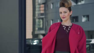 portrait confident woman with a beautiful unusual hairdress walks through the spring city. Girl on the background of modern architecture. SLOW MOTION