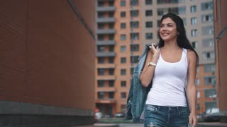 portrait of a beautiful young girl walking through the city among the buildings. young woman in jeans and a t-shirt walking in the summer city. slow motion