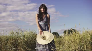 Portrait of a carefree young beautiful girl in a field with a straw hat. Young woman playfully smiling at the camera