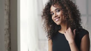 portrait of a charming hispanic girl in a black dress. curly brown girl