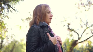 portrait of a cold woman in an autumn park. the girl sneezes and wraps herself in a scarf