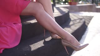 Portrait of a girl sitting on the steps. Young attractive girl in evening dress and high-heeled shoes. Beautiful female legs closeup