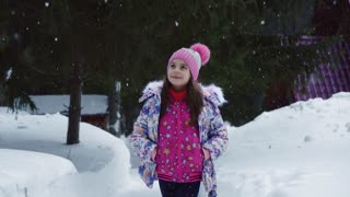 Portrait of a little girl on a walk in the winter forest. A child is walking in a winter park under a snowfall. slow motion