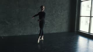 portrait of a male ballet dancer in the studio. young man dances on a dark background. slow motion