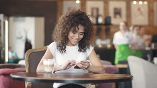 portrait of a mulatto girl in a coffee house. beautiful hispanic woman messaging on smartphone and smiling sincerely.