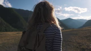 portrait of a tourist girl close-up. A traveler with a backpack and wearing sunglasses walks through the mountainous terrain.