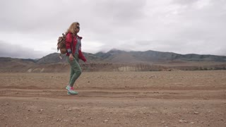 portrait of a tourist with a backpack in the mountains. girl traveler walks the mountainous terrain in inclement weather