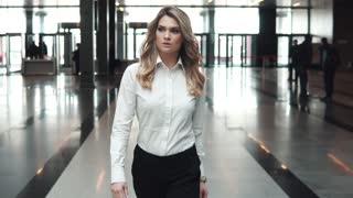 Portrait of a young business woman in a modern business center. a girl in a business suit goes to the lobby of an office building