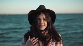 portrait of a young woman on the beach. girl in hat and autumn coat smiling and posing on camera by the water. Slow motion