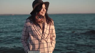 portrait of a young woman on the beach. girl in hat and autumn coat smiling and posing on camera by the water.