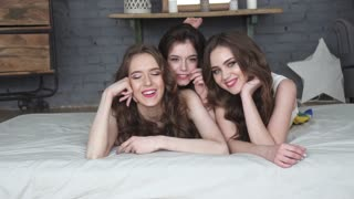 portrait of best friends. girls lying on bed smiling and looking at the camera. slow motion