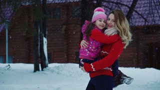 Portrait of mother and daughter. A little girl in her mother's arms in the winter forest. Mom and daughter for a walk in winter. slow motion