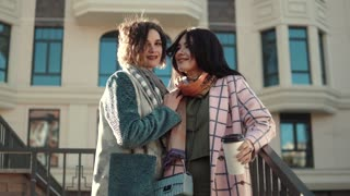 portrait of two cute young women in autumn coat against a background of modern architecture. best friends together