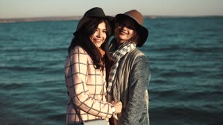 portrait of two friends on the background of autumn sea. beautiful girl smiling and happy