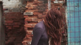 red-haired girl is impressively turning to the camera. Hair fluttering in the wind. Beautiful young girl with freckles on the background of an ancient building. slow motion