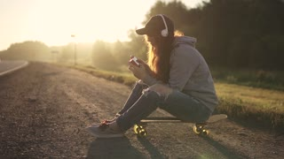 red-haired girl sits on a skateboard by the side of the road and listens to music on headphones. A girl enjoys loneliness at sunset.