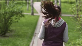 running girl. A young athlete runs through the summer park, a view from the back. The camera follows the model. Slow motion