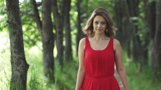 Sensual portrait of a beautiful young woman in a red dress. The girl is walking along the green alley and smiling. slow motion