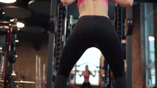sexy buttocks close-up. Young sportswoman doing sit-ups with a barbell in the gym. girl in sportswear makes strength training on her legs