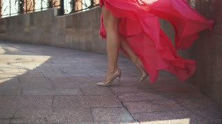 Sexy female legs in high-heeled shoes. The girl in the evening dress is walking down the street. Cloth fluttering in the wind