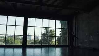 silhouette of a ballet dancer male against the background of a large window. the dancer makes a high jump. slow motion
