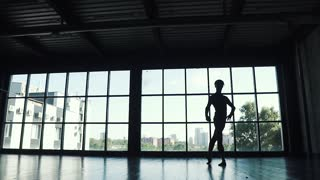 silhouette of a ballet dancer male dancing against the background of a large window. the dancer elegantly dances in the studio. slow motion