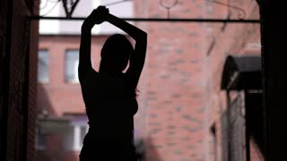 silhouette of a dancing girl on background of urban architecture. unrestrained fun outdoor