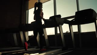 silhouette of a girl on a treadmill. young sporty girl running on the treadmill at the gym. athlete in sportswear