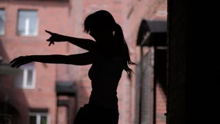 silhouette of a girl who dances and has fun on the street. unrestrained fun outdoor