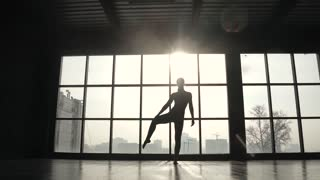 silhouette of a gymnast on the background of a large window. sports girl doing stretching before training