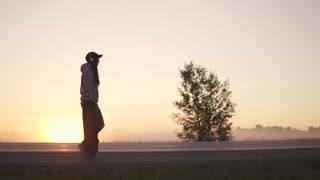 silhouette of a hipster girl with a skateboard in her hands against the backdrop of the setting sun. A girl in headphones walks along a deserted road outside the city. slow motion.