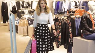 SLOW MOTION. young beautiful girl chooses clothes in shop. woman shopping