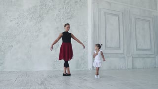 small ballerina repeats the movement in her ballet class for her teacher