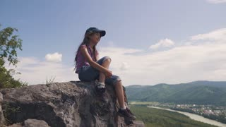 small child traveler admires the view sitting on a rock. girl tourist in the mountains