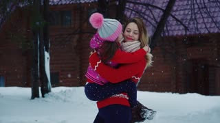 small daughter hugs and kisses her mother. Mom and child on a walk in the winter forest. parent walks with a child in a borrowed park. slow motion