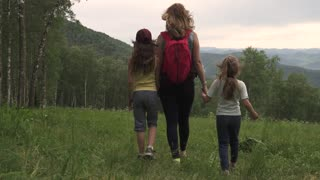 sports family travels through the mountains. A young mother of a tourist with a backpack leading her children through a forest glade