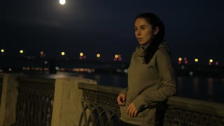 sports girl rests after jogging in the night city. athlete heart rate monitors on smart watches